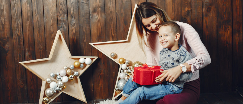 Beautiful mother in a white sweater. Family with cristmas gifts. Little boy in a gray sweater.