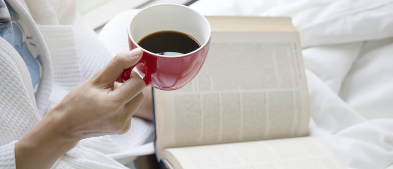 Relaxing with hot coffee and reading a book on the bed in the morning. Hobby and relaxation concept. Relaxing woman.