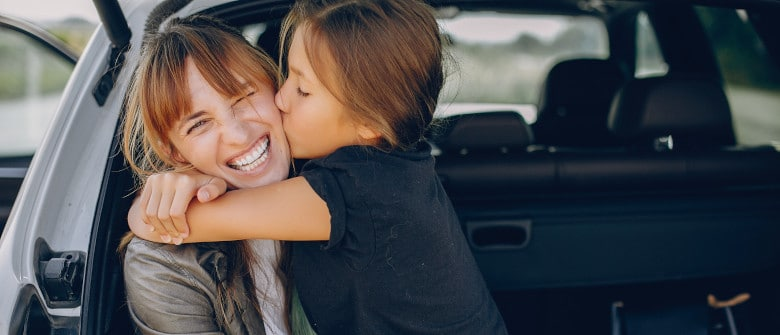 Fashionable mother with daughter. Family is sitting in the trunk. Girl in a black t-shirt